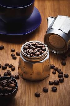 Chicchi di caffè in una caffettiera geyser su un tavolo di legno con una tazza su un piatto.