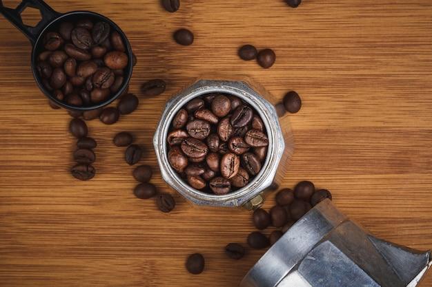 Chicchi di caffè in una caffettiera geyser su un tavolo di legno.