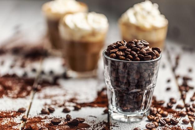 Chicchi di caffè in una tazza di vetro e sullo sfondo una tazza con caffè e panna montata