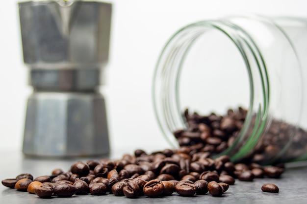 Chicchi di caffè e un barattolo di vetro con caffè sdraiato sul pavimento