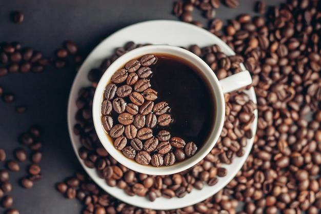 Chicchi di caffè su uno sfondo grigio e una bevanda aromatica calda su una vista dall'alto di un piattino. foto di alta qualità