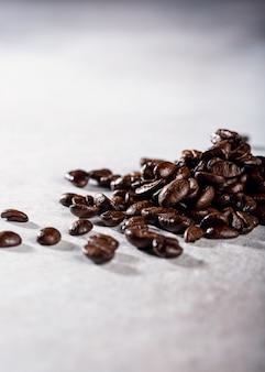 Chicchi di caffè sulla superficie grigia, copia dello spazio