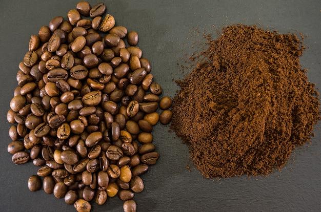 Chicchi di caffè e caffè macinato su sfondo nero