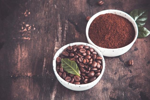 Chicchi di caffè e caffè macinato in ciotole con la foglia della pianta del caffè su un'oscurità.