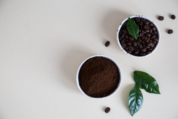 Chicchi di caffè e caffè macinato in ciotole con la foglia della pianta del caffè su una luce. copyspace per il tuo testo