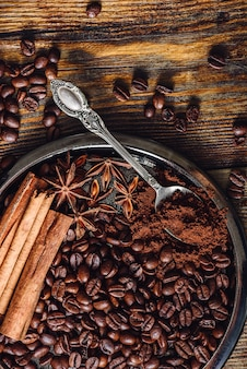 Chicchi di caffè e caffè macinato con spezie sulla piastra.