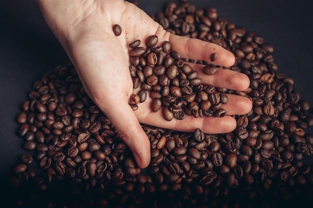 Chicchi di caffè nelle mani sparsi su uno sfondo scuro. foto di alta qualità