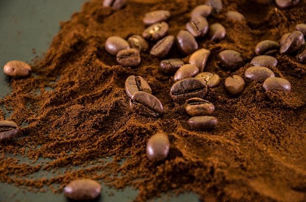 Chicchi di caffè su un mucchio di caffè macinato
