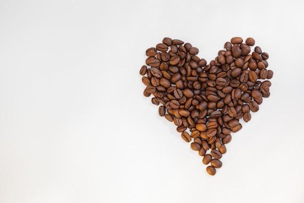 Cuore di chicchi di caffè isolato su bianco