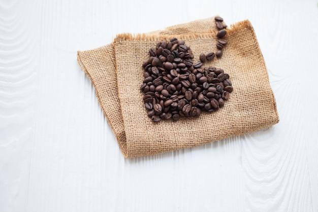 Chicchi di caffè a forma di cuore sfondo bianco isolato
