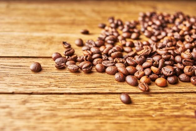 Chicchi di caffè la bevanda calda ha versato il fondo di legno dei grani. foto di alta qualità