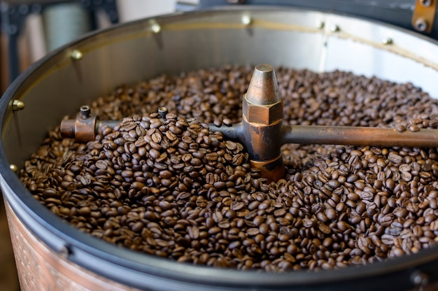 I chicchi di caffè stanno arrostendo nella macchina della torrefazione nella caffetteria.