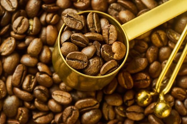 Chicchi di caffè in misurino e clip borsa contro caffè appena tostato, profondità di campo