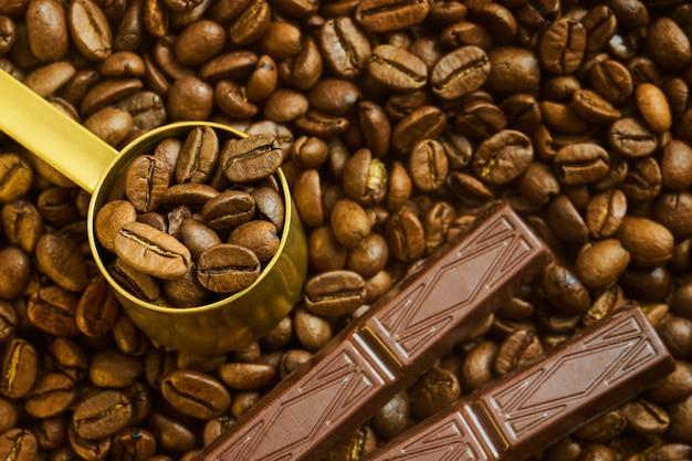 Chicchi di caffè in un misurino e cioccolato su una superficie di caffè appena tostato