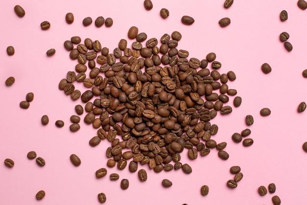 Chicchi di caffè sul rosa