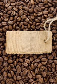 Chicchi di caffè e cartellino del prezzo con lo spazio della copia