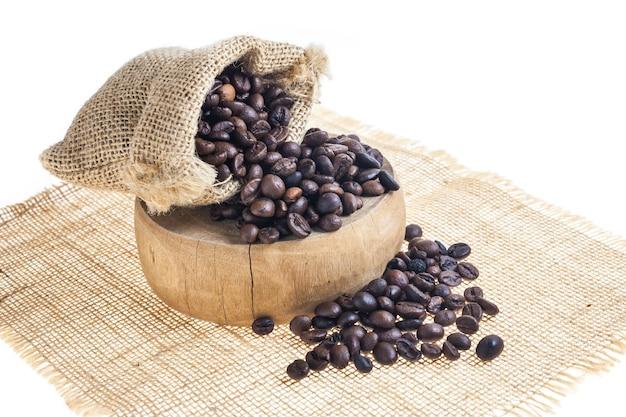 Chicchi di caffè in sacco sul tagliere di legno.