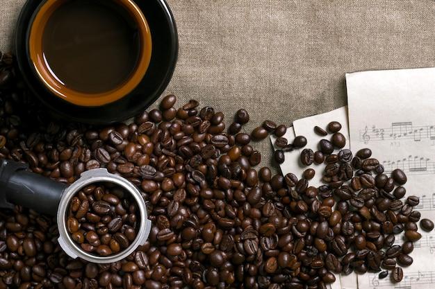 Spartiti di chicchi di caffè e tazza di caffè su uno sfondo di tela