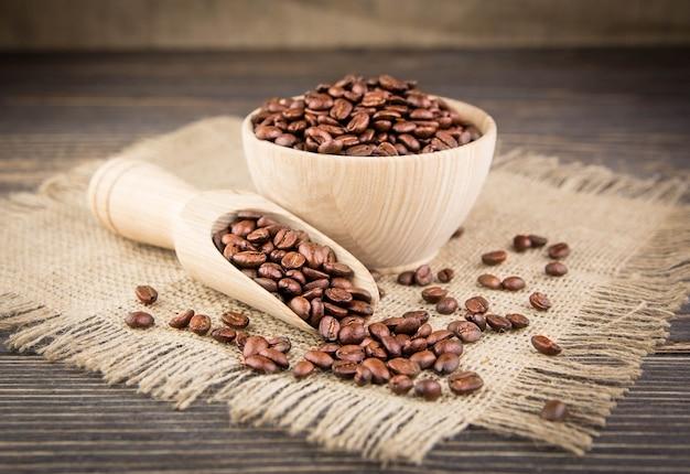 Chicchi di caffè sulla tovaglia sulla tavola di legno