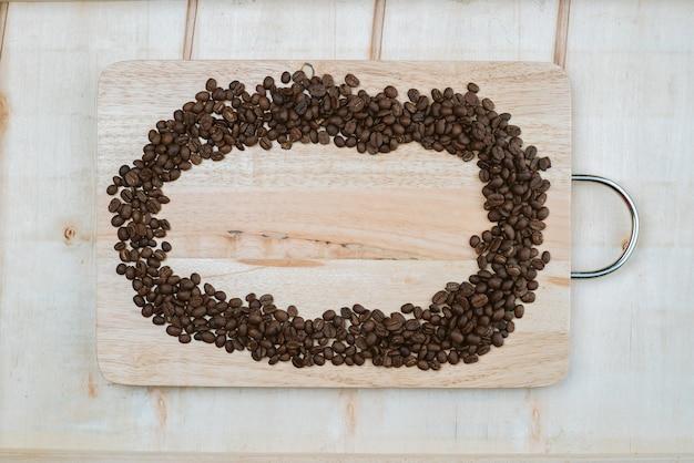 Chicchi di caffè che sono racchiusi attorno a una tavola di legno