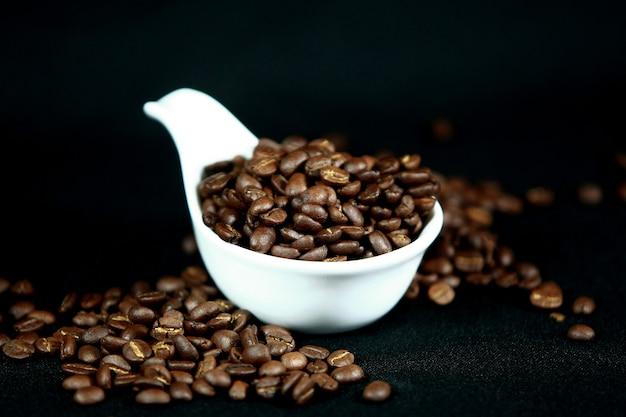 Chicchi di caffè in una tazza bianca, fine in su, vista superiore