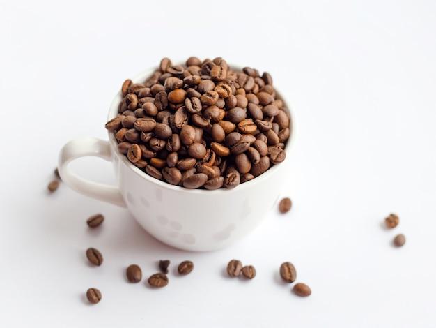 Chicchi di caffè in tazza bianca isolata su superficie bianca, concetto di bevande