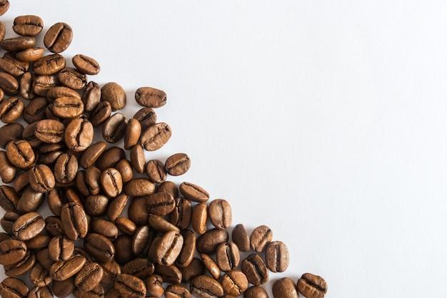 Chicchi di caffè su una pubblicità del caffè di superficie bianca
