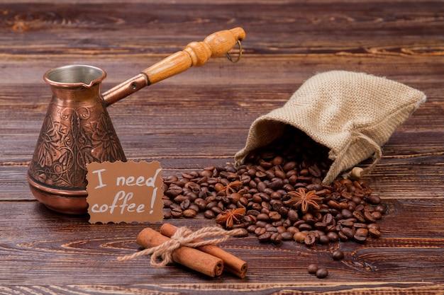 Chicchi di caffè con cannella e pentola sul tavolo