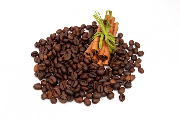 Chicchi di caffè con bastoncini di cannella su uno spazio bianco