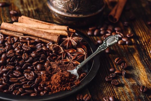 Chicchi di caffè con cucchiaiate di caffè macinato, bastoncini di cannella e anice stellato cinese su piastra metallica. alcuni fagioli sparsi sulla tavola di legno e cezve sullo sfondo.