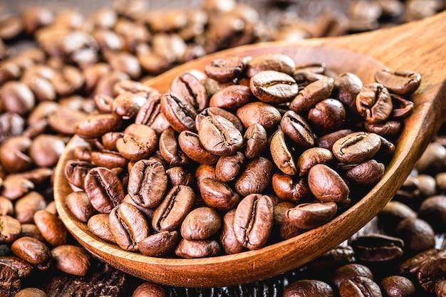 Chicchi di caffè con cucchiaio di legno, caffè arabo selezionato in alta risoluzione