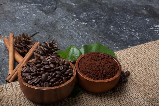 Chicchi di caffè in tazza di legno sulla foglia verde, pino su tela da imballaggio su pietra nera strutturata