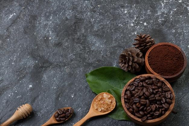 Chicchi di caffè in tazza di legno sulla foglia verde, zucchero in cucchiaio di legno, pino sulla pietra nera