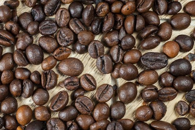 Chicchi di caffè su fondo di legno.