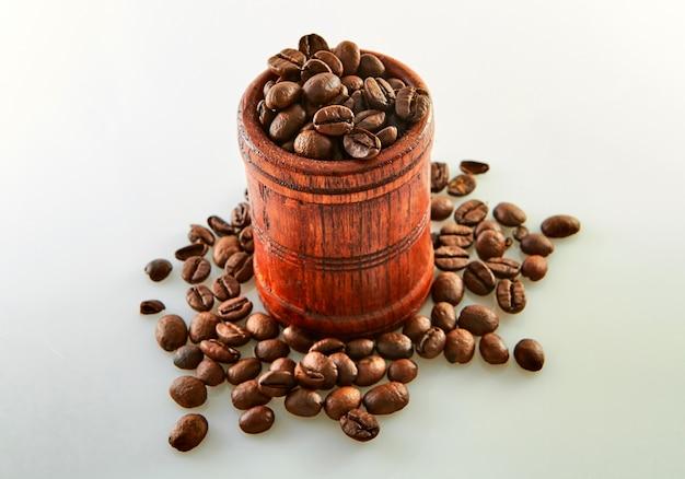 Chicchi di caffè in un barilotto di legno isolato