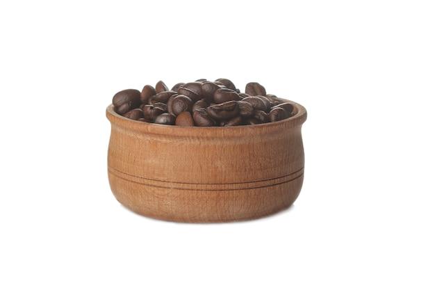 Chicchi di caffè in una ciotola di legno su uno sfondo bianco isolato. chicchi di caffè tostati