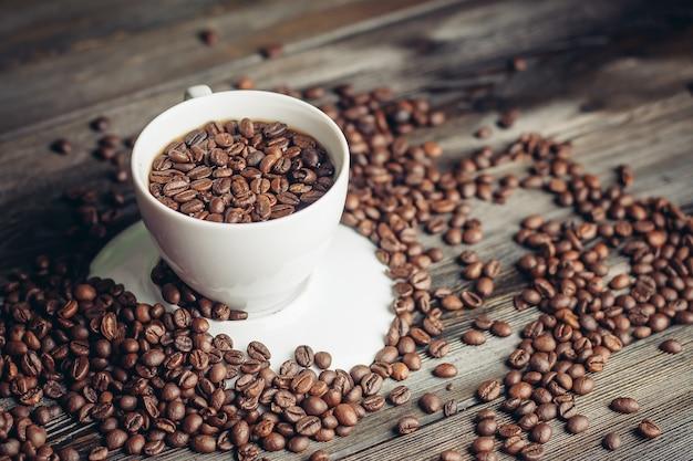 Chicchi di caffè su un legno e una tazza su una fotografia macro close-up piattino.