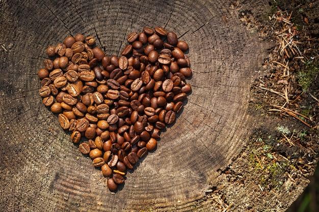 Chicchi di caffè su una vecchia struttura in legno a forma di cuore