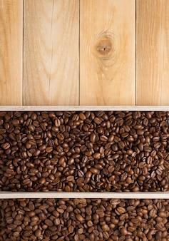 Chicchi di caffè in fondo della scatola di legno della plancia, vista dall'alto