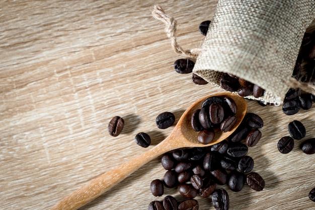 Chicchi di caffè sul cucchiaio di legno con il fondo della tavola di legno. vista dall'alto con copyspace