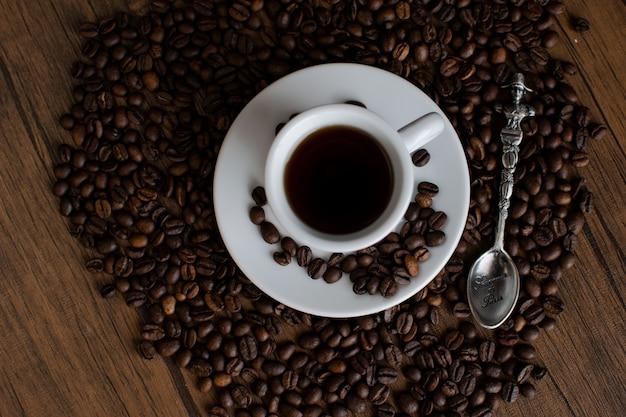 Chicchi di caffè su un tavolo di legno, utensili da caffè bianco, una tazza di caffè espresso