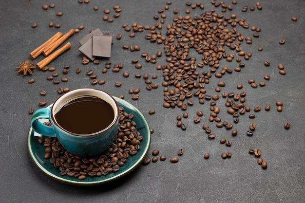 Caffè in tazza blu e chicchi di caffè, bastoncini di cannella e pezzi di cioccolato su sfondo scuro