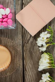 Caffè, libro, fiori e uova di pasqua sulla tavola di legno