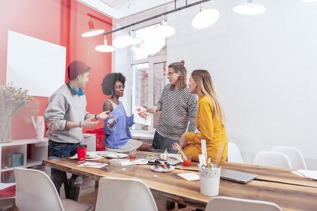 Caffè e brainstorming. quattro studenti intelligenti moderni che bevono caffè e fanno brainstorming