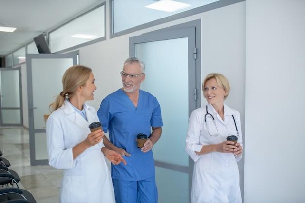 Pausa caffè. gruppo di operatori sanitari professionisti che godono del caffè nel corridoio