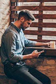 Pausa caffè. vista laterale del bel giovane premuroso che tiene in mano lo smartphone e lo guarda mentre è seduto vicino alla finestra nell'interno del loft con una tazza di caffè in mano
