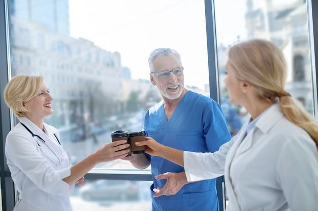 Pausa caffè. sorridente operatori sanitari che bevono caffè, avendo una conversazione amichevole