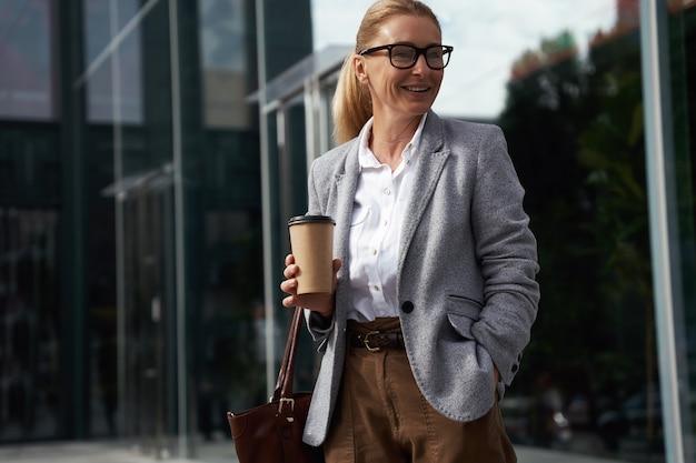 Pausa caffè elegante donna d'affari felice che indossa occhiali classici che tengono tazza di caffè e