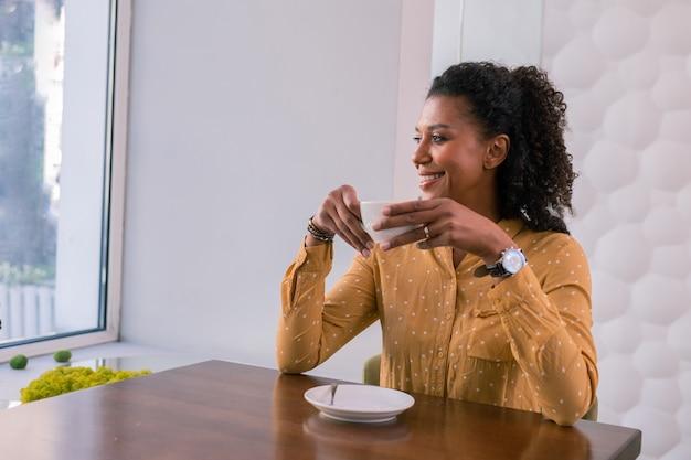 Pausa caffè. elegante imprenditrice di successo indossando camicetta maculata gialla godendo la sua pausa caffè nella caffetteria