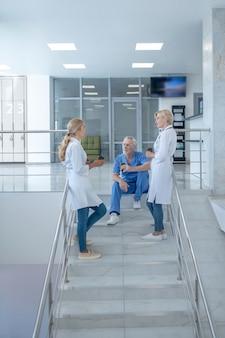 Pausa caffè. squadra di operatori sanitari che bevono caffè sulle scale
